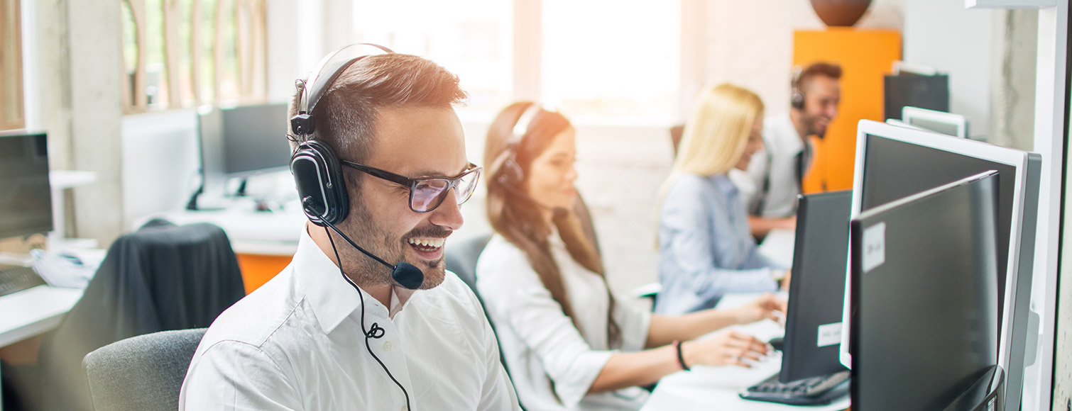 Smiling man in business wear with headset working on a desktop computer as a customer support executive