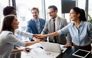A cheerful group of business professionals placing hands one above another symbolizes teamwork