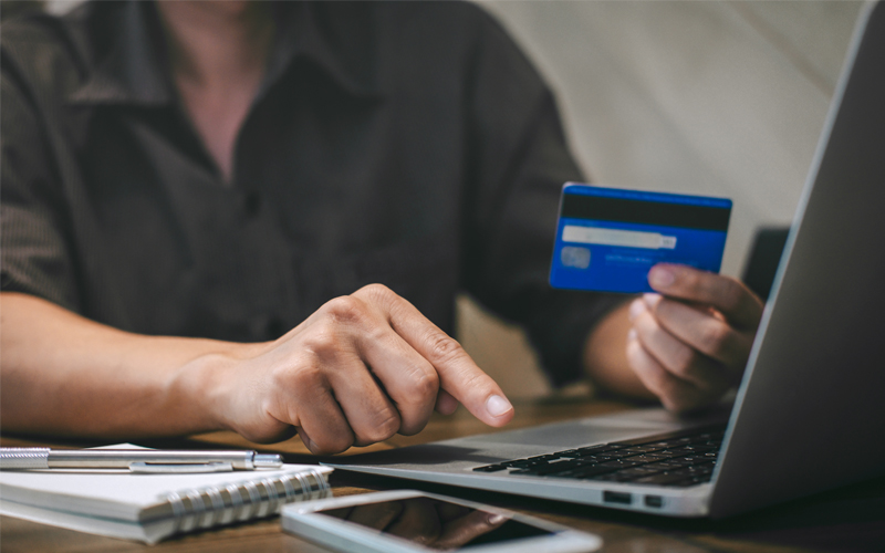 Human hand holding credit card and making an online payment through laptop